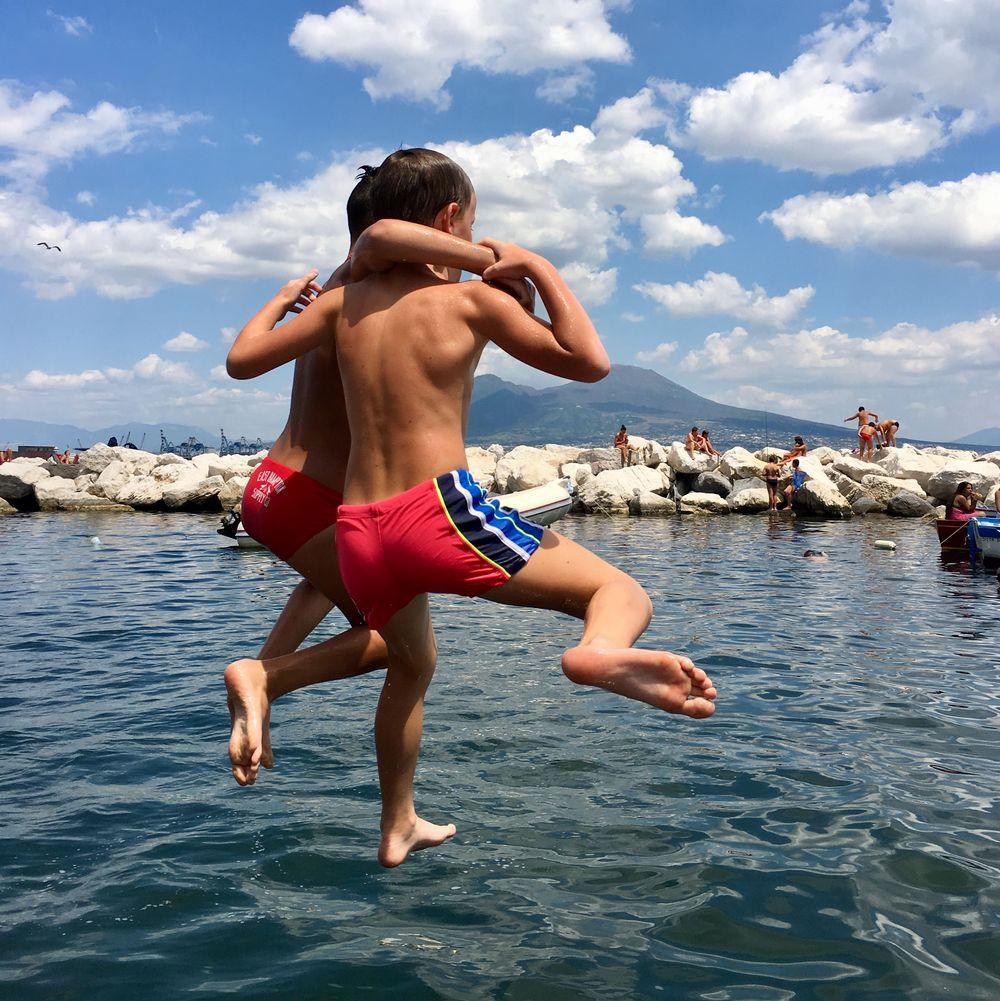 kinderen springen in de zee in napels